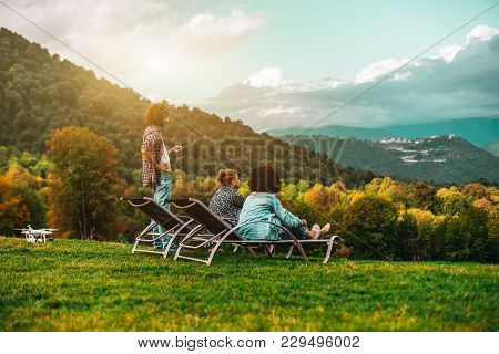 Group Of Three Friends: Two Girls Are Chilling On Daybeds On The Lawn And One Bearded Man Standing N