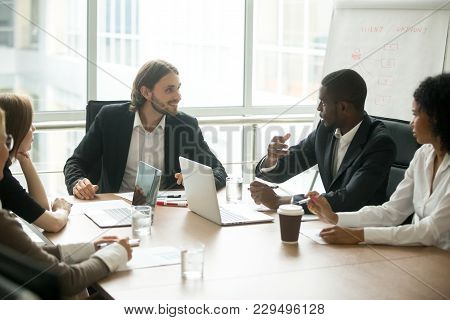 Diverse Business Executives Discussing Project Sitting At Conference Table, Multiracial Partners Tal