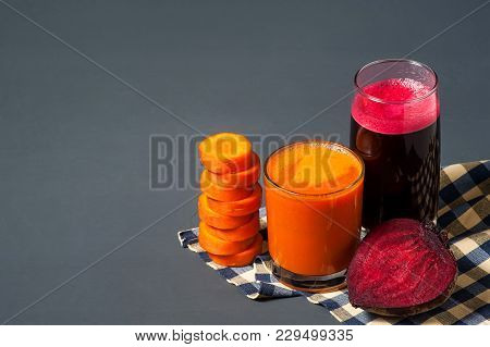 Natural Juices From Carrots And Beets. The Juice Is Poured Into A Clear Glass, Next To The Chopped C