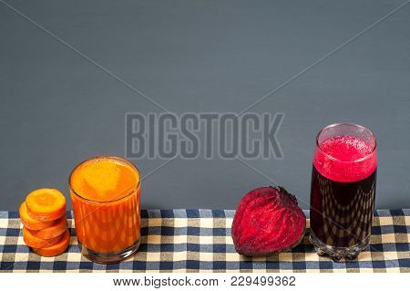 Natural Juices From Carrots And Beets. The Juice Stands On A Tablecloth, Next To Sliced Carrots And