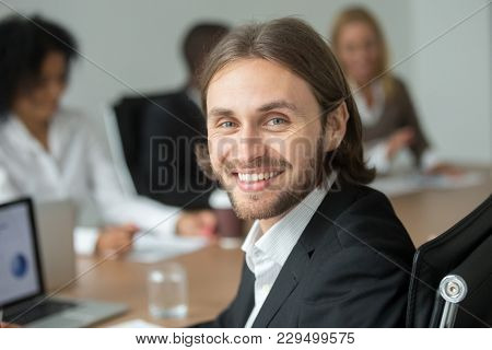 Smiling Attractive Young Businessman Wearing Suit Looking At Camera With Diverse Partners At Meeting
