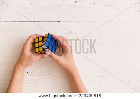 Moscow, Russia, August 24 2017: Rubik's Cube In Woman's Hands, Closeup, White Wooden Background. Gir