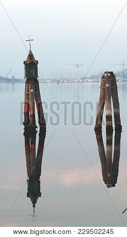 Chioggia, Italy. Venetian Buoys In The Harbour. Reflection