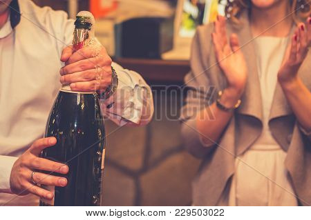 Bride And Groom Toasting At Wedding Party. Man Opening Bottle Of Champagne While Woman Clapping And