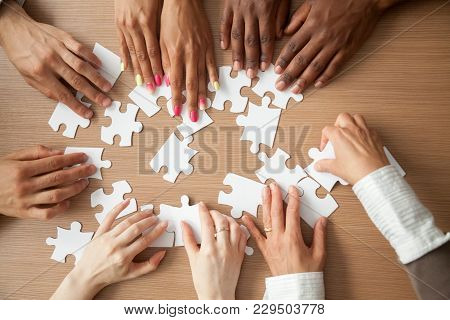 Hands Of Diverse People Assembling Jigsaw Puzzle, African And Caucasian Team Put Pieces Together Sea
