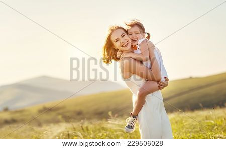 Happy Family In The Summer Outdoors.   Mother Hug Child Daughter And Laughing