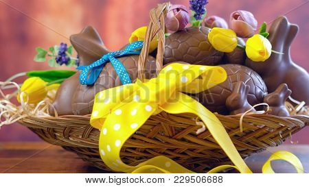 Happy Easter Hamper Of Chocolate Eggs And Bunny Rabbits In Large Basket With Silk Tulips On Dark Woo