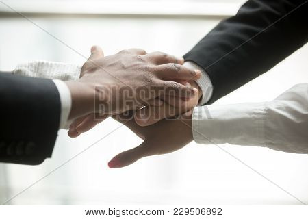 African And Caucasian Partners Join Hands In Pile Together, Motivated Multiracial Business Team Prom