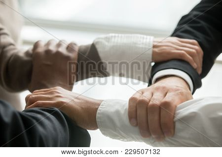Four Multiracial Business People Holding Each Others Wrists, Diverse Partners Join Hands Together As