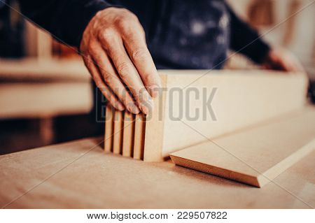 A Carpenter Works On Woodworking The Machine Tool. Toned Image.