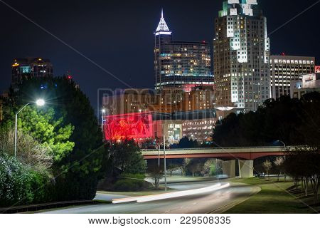 A dark cityscape view of downtown Raleigh, North Carolina convention area with traffic trails.