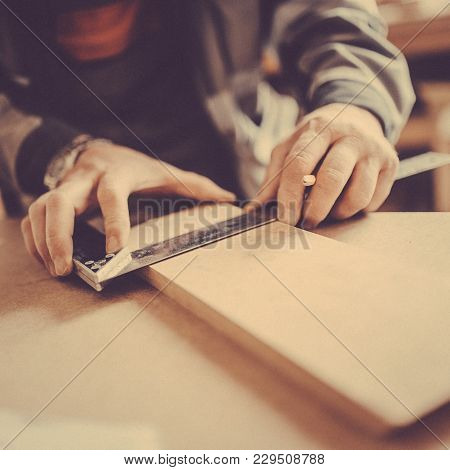 A Carpenter Uses A Framing Square For Marking A Hole In A Furniture Part. Toned Image.