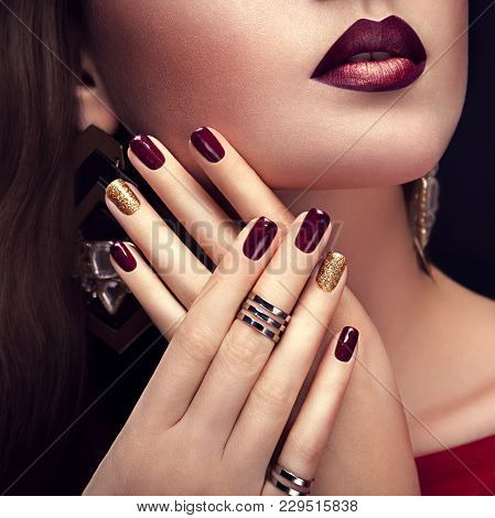 Beautiful Woman With Perfect Make-up And Burgundy And Golden Manicure Wearing Jewellery On Black Bac