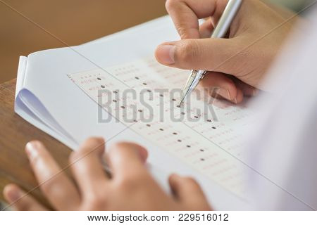 Education Test Concept : Blur Of Hand Student Holding Pen For Testing Exams Writing Answer Sheet Or