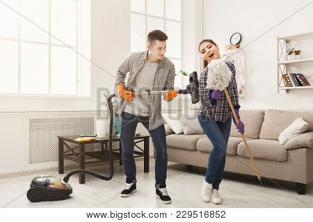 Young Couple Cleaning Home, Playing With Mop And Vacuum Cleaner, Having Fun In Living-room. Housekee