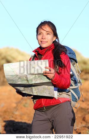 Hiking woman in nature holding map outdoors in nature. Smiling happy hiker in desert mountain landscape.