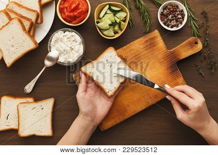 Woman Cooking Tasty Sandwich With Cream Cheese, Top View. Female Hands Spreading Bruschetta Topping