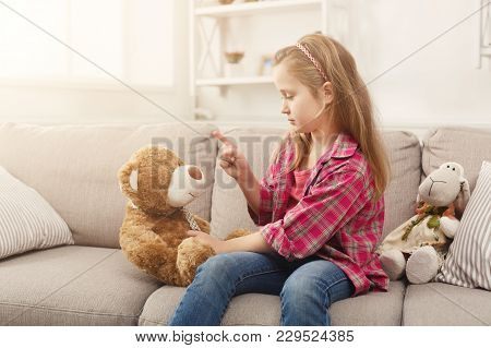 Serious Little Girl Educating Her Teddy Bear And Wagging Her Finger. Cute Child Playing Games And Ha