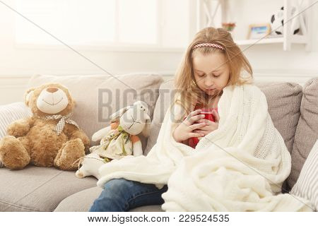Pretty Little Girl Drinking Tea, Sitting On Sofa Wrapped Up In White Knitted Blanket. Cute Pensive K