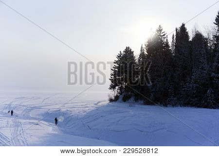 Ice-covered Mouth Of A Winter River Flowing Into A Lake, In A Frosty Haze, With A High Shore And Peo