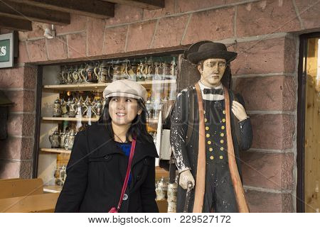 Asian Thai Woman Travel And Posing With Wooden Man Statue At Souvenir Gift Shop In Black Forest In G