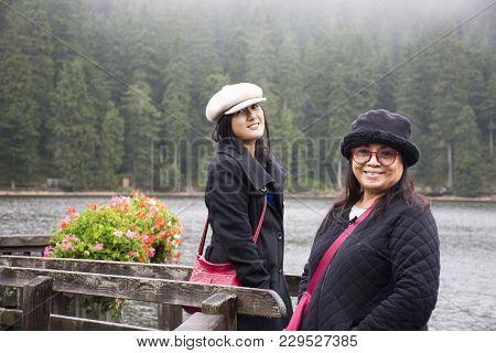 Asain Thai Women Mother And Daughter Travel And Posing At Waterfront Wooden Bridge At Mummelsee Lake
