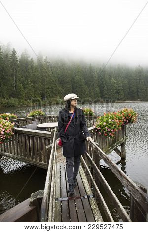 Asian Thai Woman Travel And Walking At Waterfront Wooden Bridge At Mummelsee Lake While Raining In B