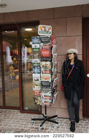 Asian Thai Woman Posing With Shelf Book At Gift Shop In The Forest At Black Forest Or Schwarzwald At