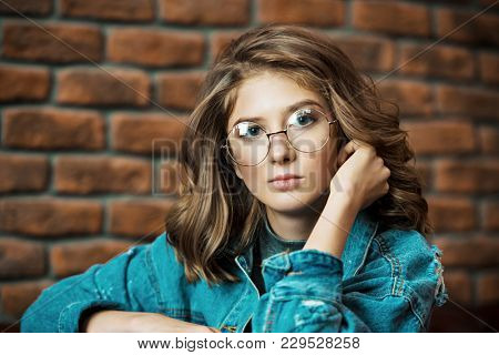 Portrait of a cute girl teenager wearing spectacles. Glasses for a modern young generation. Beauty, fashion.