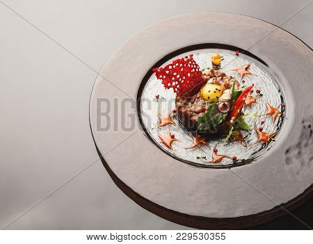 Exclusive Restaurant Food. Traditional Appetizer - Raw Veal Tartare With Sauce, Quail Egg, Greens, V