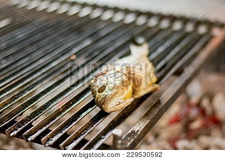 Grilled Fish With Lemon On Iron Grill. Dorado Fish Barbecued On The Grill At Restaurant. Preparation