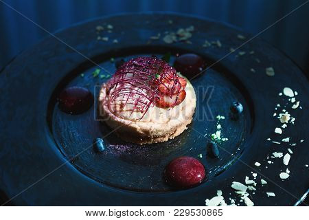 Modern Restaurant Dessert Closeup. Lemon Cheesecake With Berry Spheres And Caramel Decoration Served