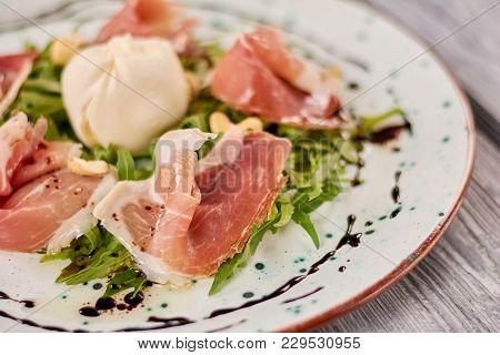 Prosciutto And Arugula Salad With Burrata. Close Up Of Appetizing Salad With Arugula, Prosciutto And
