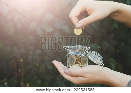 Hand Putting Coins In Glass Jar With Save Label On Green Leaves Background. Money Saving For House,
