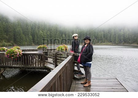 Asain Thai Women Mother And Daughter Travel And Posing At Mummelsee Lake While Raining In Black Fore