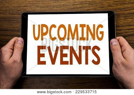Hand writing text caption Upcoming Events. Business concept for Appointment Agenda List Written tablet laptop, wooden background with businessman hand, finger holding PC. poster