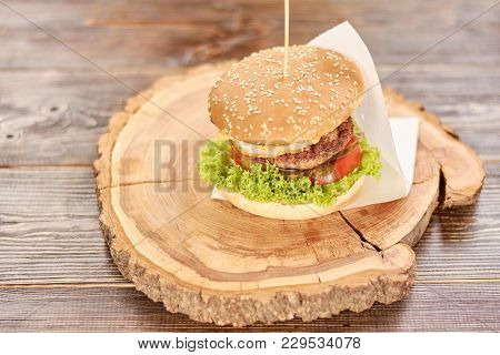 Big Tasty Burger On Round Wood. Big Hamburger With Beef Cutlet And Fresh Vegetables On Natural Wood.