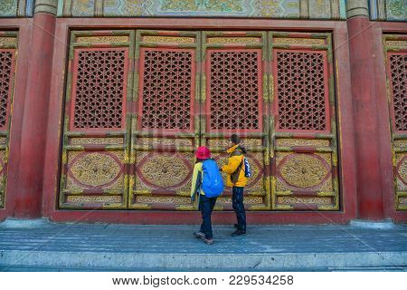 Beijing, China - Mar 1, 2018. People Looking At Ornate Wooden Door With Tile Trim Of The Forbidden C