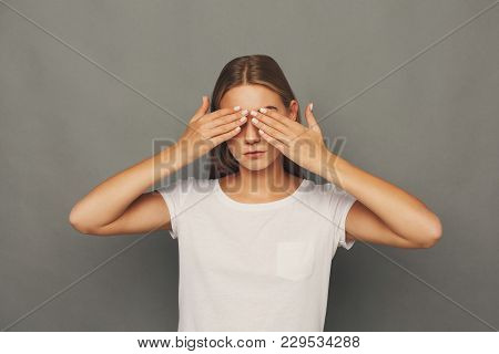 See No Evil Concept. Portrait Of Young Scared Woman Covering Eyes With Hands, Gray Studio Background