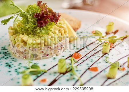 Beautifully Served Dish. Appetizing Salad With Herring, Avocado And Toasts Served With Lettuce And L