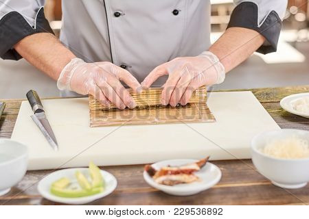Cook Making A Sushi Roll With Bamboo Mat. Chef Sat Professional Kitchen Preparing Sushi. The Process