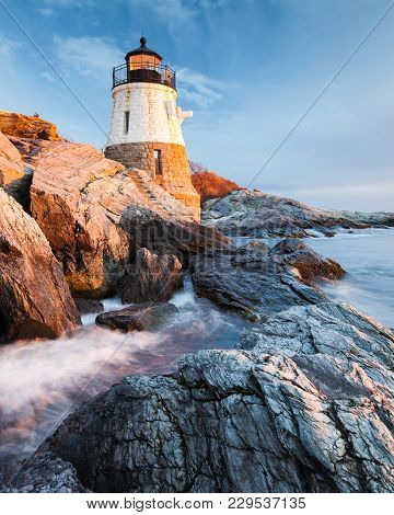 Small Castle Hill Lighthouse Sits On The Rocky Coastline Of Newport, Rhode Island At Sunset With The
