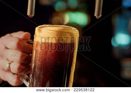 Bartender Hand Pouring Fresh Beer. Close Up Barman Hand At Beer Tap Pouring Beverage In Glass. Pouri