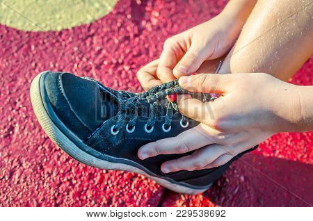 Shoelace Being Tied Into Braid. Fashion And Style With These Sneakers. Solution To Dangling Shoelace