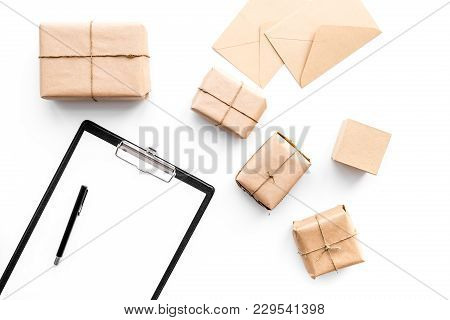 Parcel Delivery Concept. Wrapped Boxes And Pad On Whote Backgroyund Top View.