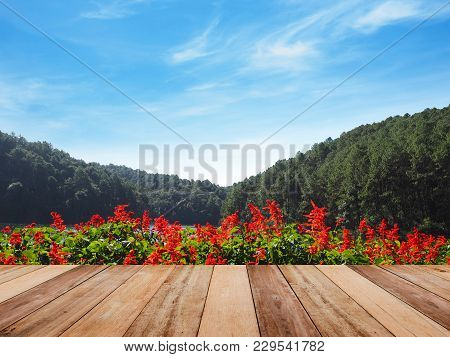 Wood Table Top Over Red Salvia Flower At Lake And Green Forest Against Blue Sky.