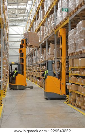 Two Forklift Stacker Trucks In Distribution Warehouse
