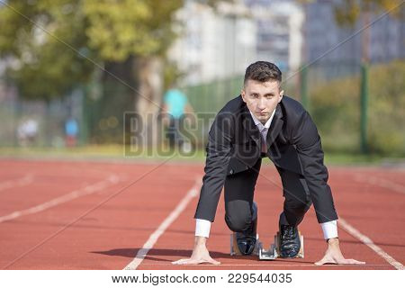 Business Man In Suit Starting And Preparing To Run On The Competition Running Performance Track.