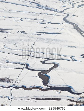 Aerial View Of The Tundra In The Winter. Impassable Snowy Plain Crossed By Some Creeks. Power Line I