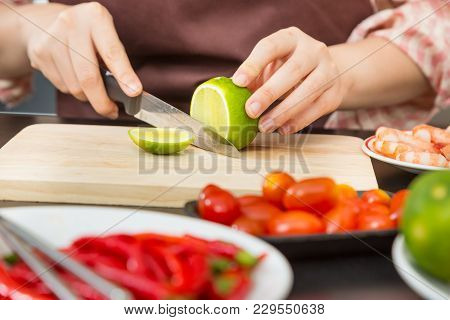 Female Hands Cutting Green Lime On Wooden Cutting Board In Her Home Kitchen, Surrounded By Other Foo